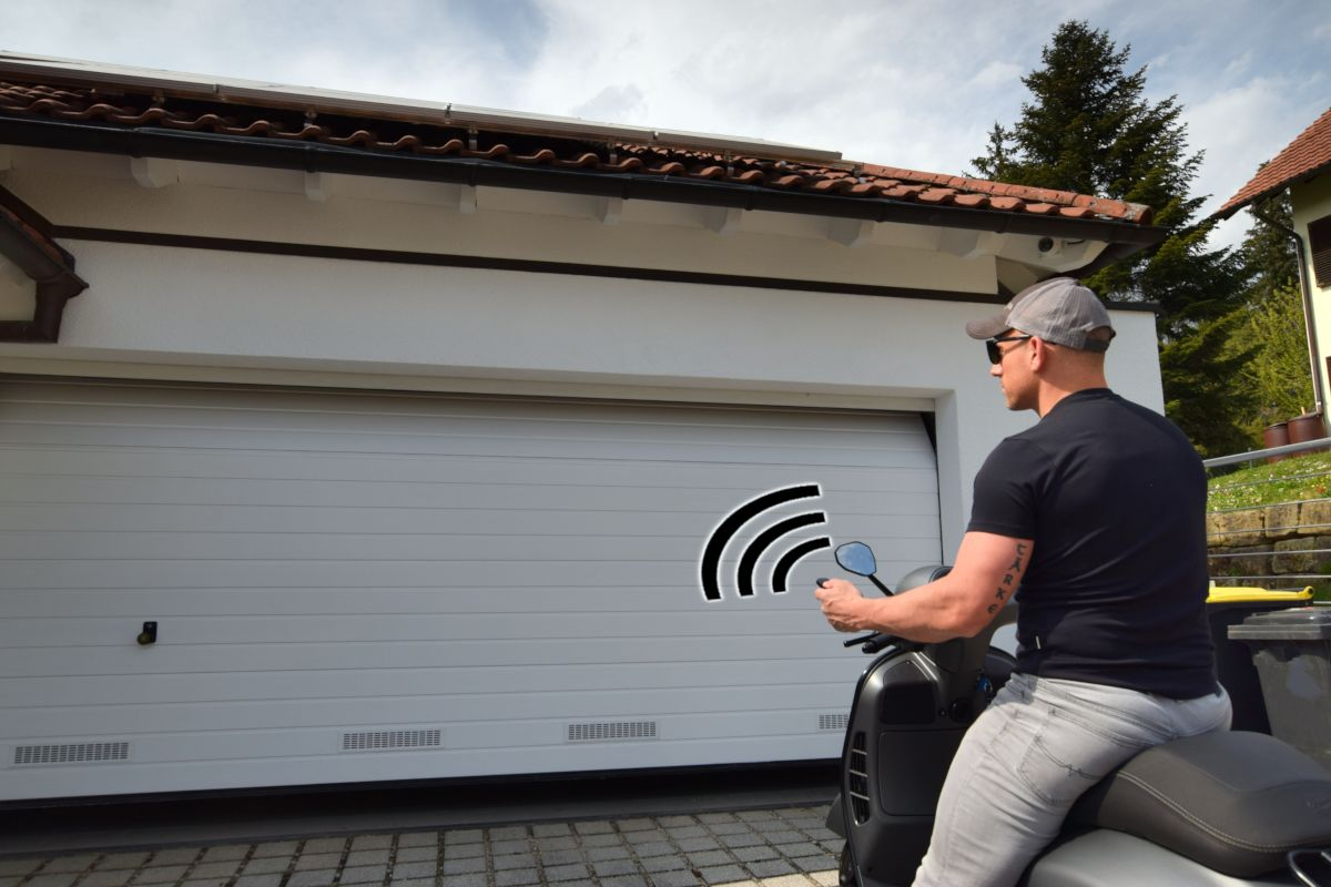 Mann auf Roller vor Garagentor beim Öffnen mit Handsender mit Funkwellen