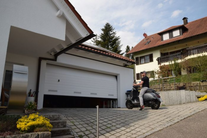 Hauseinfahrt mit öffnendem Sektionaltor in weiß