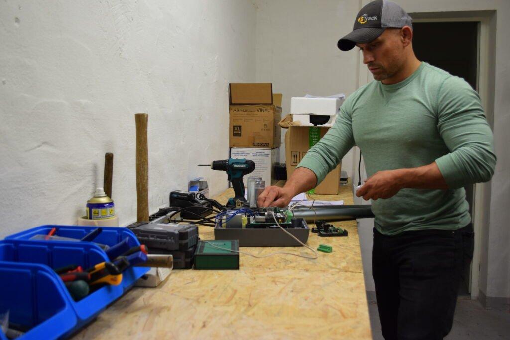 Mann in Werkstatt repariert einen Garagentorantrieb