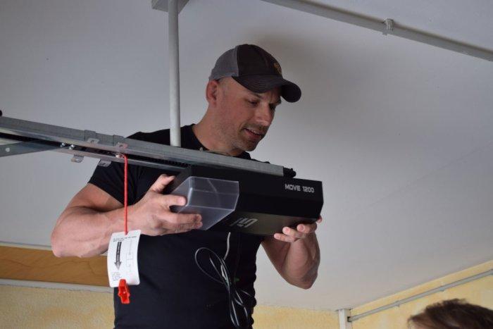 Mann installiert Garagentorantrieb an Sektionaltor